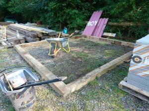 Her skal være et lille haveskur. 15x15 cm stolper og noget sand i, og så fliser.