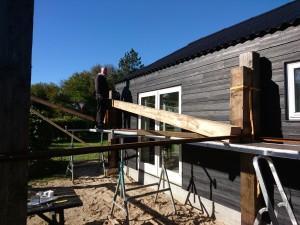 Claus i gang med at løfte stolper op, 20x20 og næsten 5 meter, ren kernetræ.. Vi gætter på pmkring 200 kg pr pind..