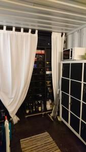 Vi sætter gardiner op.. dette som opdeling i containeren, og gemmer de store brune reoler med værktøj